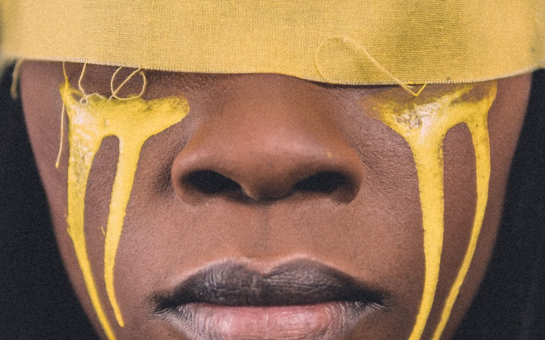 Black woman with a yellow strip around her eyes. Yellow paint like tears is painted down her face to her chin.
